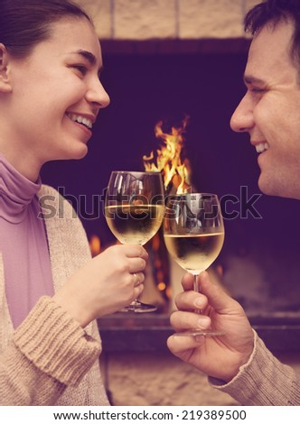Portrait of a romantic young couple toasting wineglasses in front of lit fireplace - stock photo
