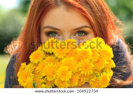 Portrait of a romantic young woman with a bouquet of dandelions outdoors. - stock photo