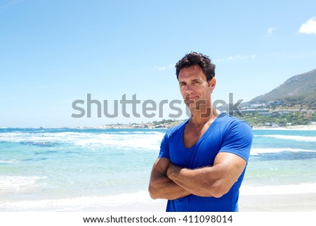 Portrait of a rugged good looking man standing with arms crossed at the beach  - stock photo