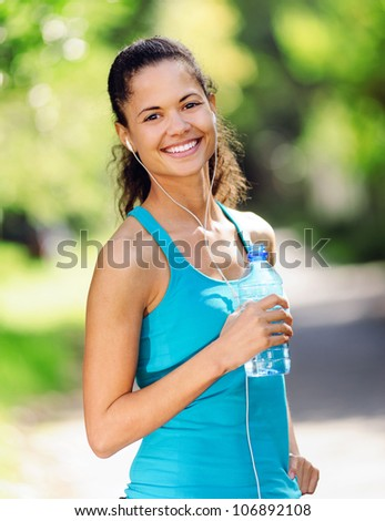 Portrait of a runner listening to music on headphones and holding water bottle. healthy wellness fitness lifestyle. - stock photo