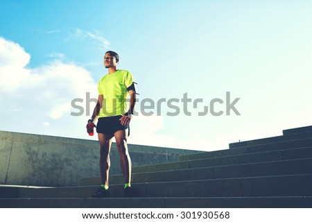Portrait of a runner man with armband on the arm rest after jogging while standing on ladder against the sky background with copy space area for your text message information,sportsman taking a break  - stock photo