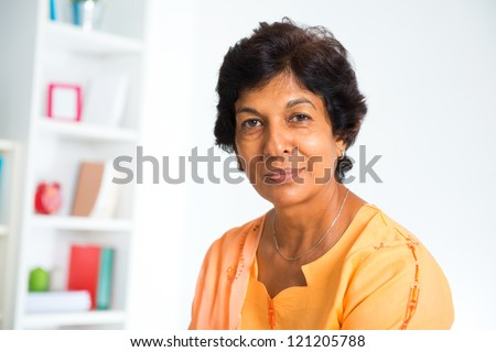 Portrait of a 50s Indian mature woman smiling, isolated on white background - stock photo