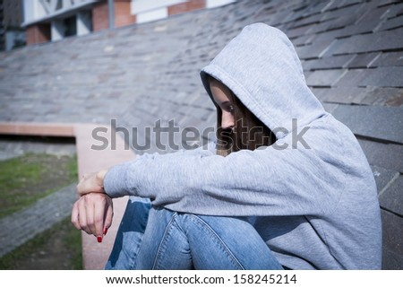 portrait of a sad and lonely young girl - stock photo