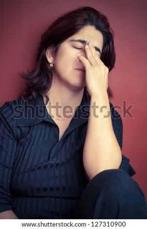 Portrait of a sad and stressed hispanic woman suffering a headache - stock photo