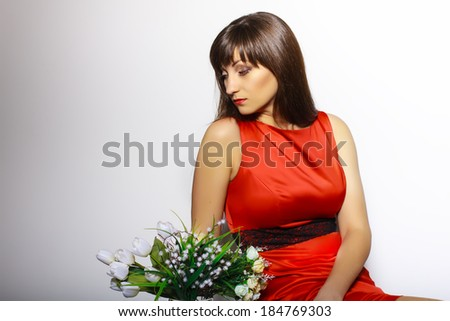Portrait of a sad Beautiful girl in a red dress whith spring bouquet on a white background