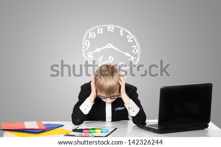 Portrait of a sad boy with the laptop and the drawn clock - stock photo