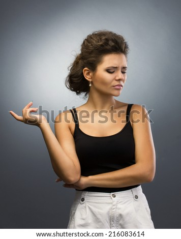 portrait of a sad brunette girl in black and white casual  clothing looking down on grey background
