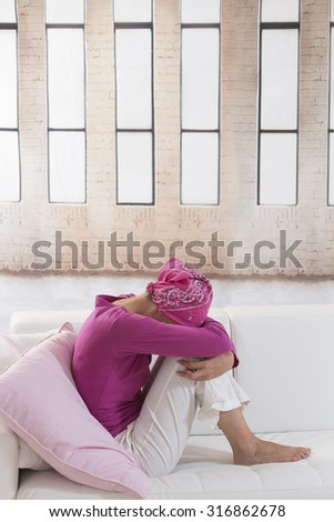 portrait of a sad depressed woman hiding her face - stock photo