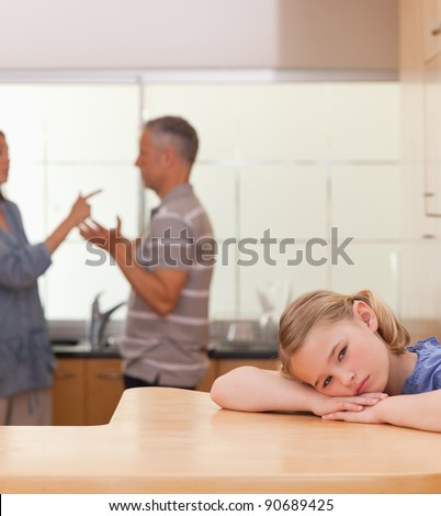Portrait of a sad girl listening her parents arguing in a kitchen - stock photo