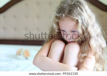 portrait of a sad girl sitting on a bed in the bedroom  with a toy - stock photo