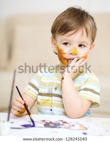 Portrait of a sad little boy messily playing with paints