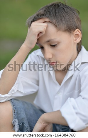 Portrait of a sad little boy outdoors in summer - stock photo