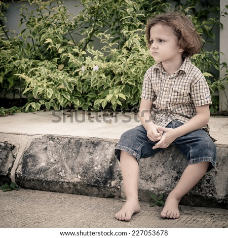 Portrait of a sad  little boy sitting on the road at the day time - stock photo