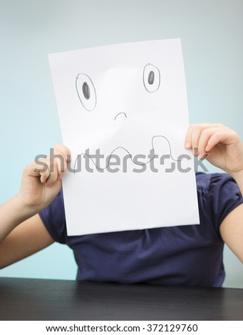 Portrait of a sad little child holding picture - stock photo