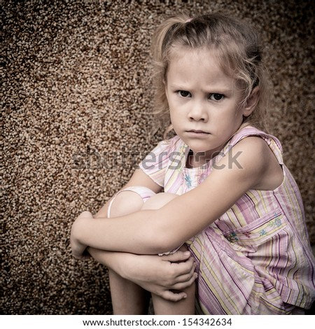portrait of a sad little girl sitting near the wall - stock photo