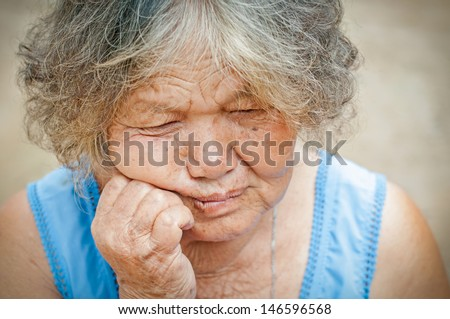 Portrait of a sad old woman with a sad nostalgic expression.
