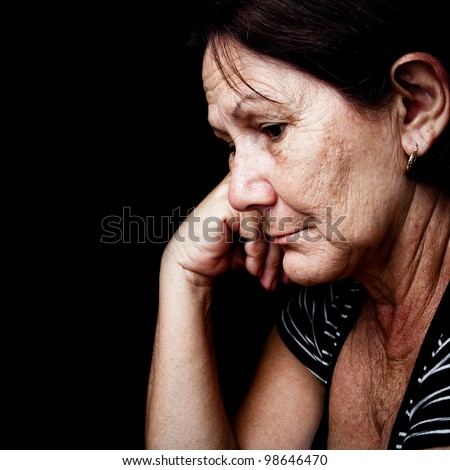 Portrait of a sad old woman with a sad nostalgic expression isolated on black - stock photo