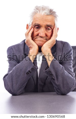 Portrait of a sad senior man lost in deep thoughts with both hands on face against white - stock photo