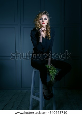 Portrait of a sad woman. Fashionable ladies. Red lips, blue eyes, green lily of the valley bouquet. Toned image. Females model sitting on a bar stool against the dark wall. Fashion concept. - stock photo