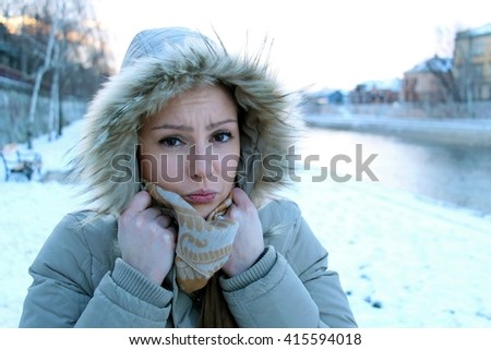 Portrait of a sad young brunette girl tucked under her furry jacket hood trying to get warm because she is freezing out in the cold winter day. - stock photo