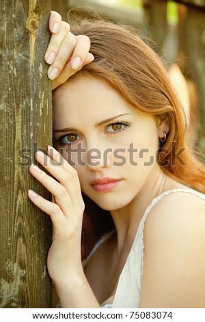 Portrait of a sad young girl who relies on the wooden wall