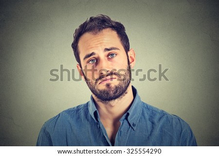 Portrait of a sad young man isolated on gray wall background  - stock photo