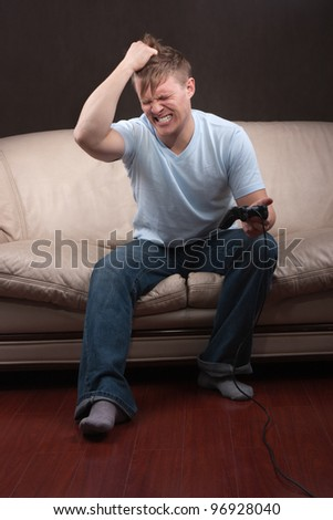 portrait of a sad young man playing video games on gray background