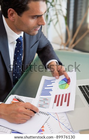 Portrait of a sales person studying statistics in an office - stock photo