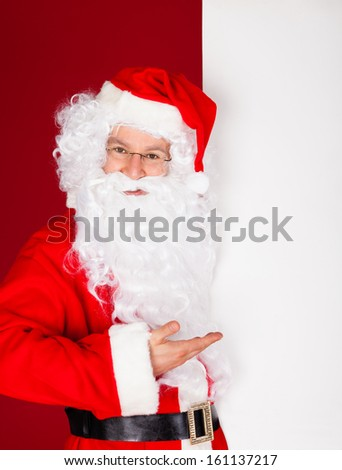 Portrait of a santa holding blank placard over red background