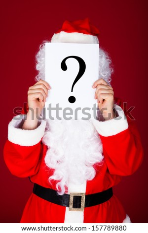 Portrait of a santa holding question mark in front of his face - stock photo