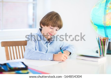 Portrait of a school boy doing his homework at home - stock photo