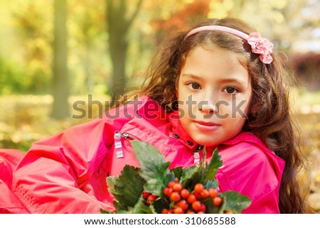Portrait of a school girl holding bouquet of ripe ash berries, sitting in a yellow sunny park - stock photo