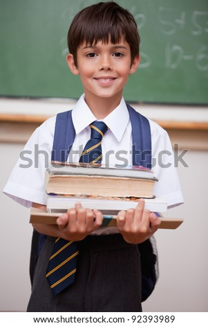 Portrait of a schoolboy holding books in a classroom - stock photo