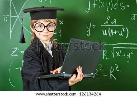 Portrait of a schoolboy in big round spectacles and academic hat at a classroom. - stock photo