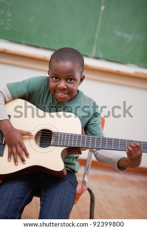 Portrait of a schoolboy playing the guitar in a classroom - stock photo