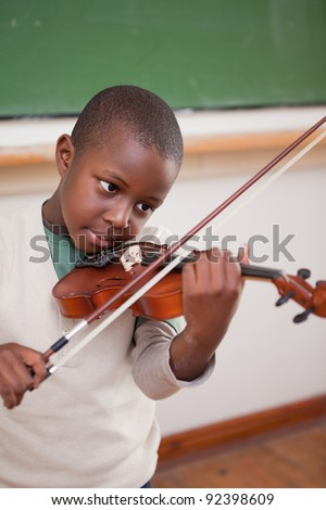 Portrait of a schoolboy playing the violin in a classroom - stock photo