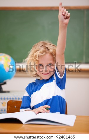 Portrait of a schoolboy raising his hand in a classroom - stock photo