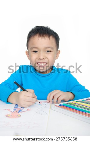 Portrait of a schoolboy sitting and writing in notebook. - stock photo