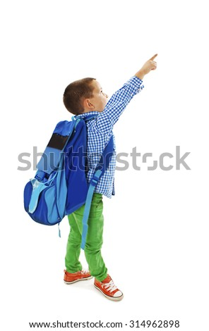 Portrait of a schoolboy with big backpack is pointing up. Isolated on white background  - stock photo