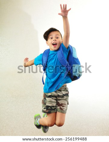 Portrait of a schoolchild with backpack leaping . Childhood, education, learning concept - stock photo