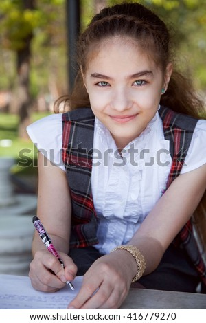 Portrait of a schoolgirl making her homework and taking notes outdoors in the summer. - stock photo