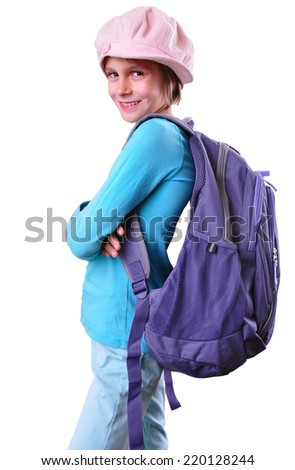 Portrait of a schoolgirl of grade school with backpack and cap posing. Isolated over white background. Education concept - stock photo
