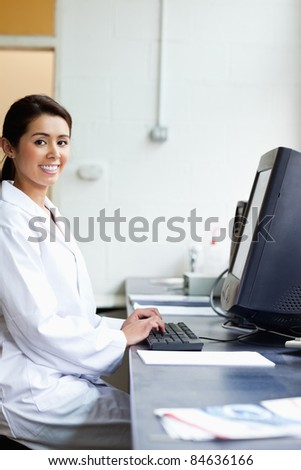 Portrait of a science student with a monitor looking at the camera