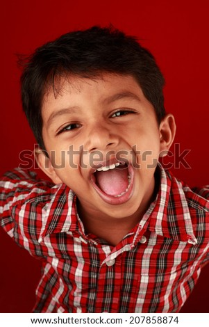 Portrait of a screaming boy in red background - stock photo