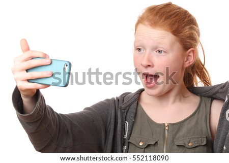 Portrait of a screaming teenage girl with mobile phone on white background