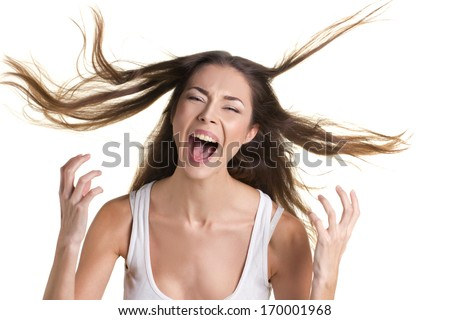 portrait of a screaming young woman in white tank top with long flying hear on white background - stock photo
