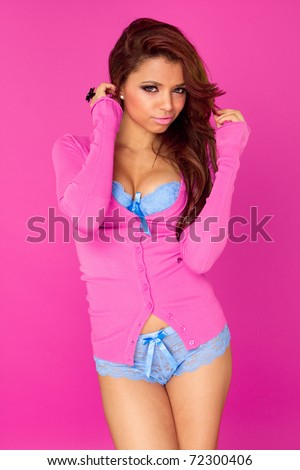Portrait of a seductive female model in pink blue lingerie against pink background - stock photo