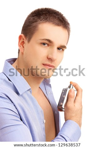 Portrait of a seductive young man spraying perfume
