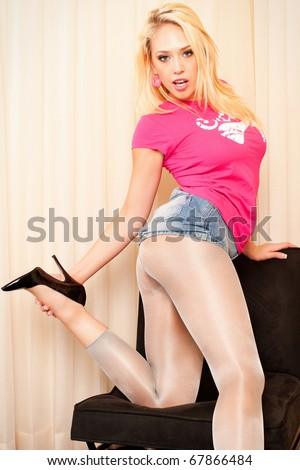 Portrait of a seductive young woman in casuals wearing stockings and high heels - stock photo