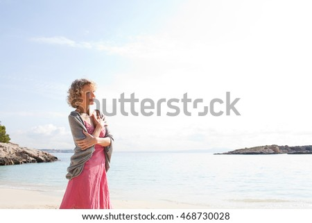 Portrait of a senior beautiful woman on beach destination shore smiling joyful looking ahead contemplating clear blue sea, aspirational travel lifestyle, outdoors nature.